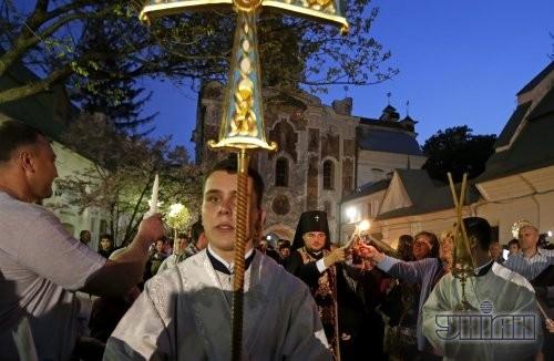 Священник раздает Благодатный огонь прихожанам на территории Киево-Печерской Лавры