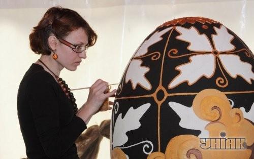 Женщина разрисовывает писанку
