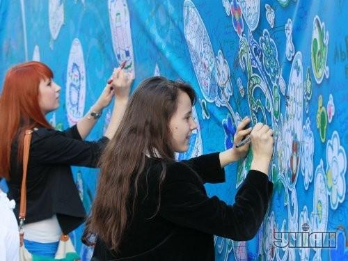 Девушки рисуют орнаменты писанок на холсте