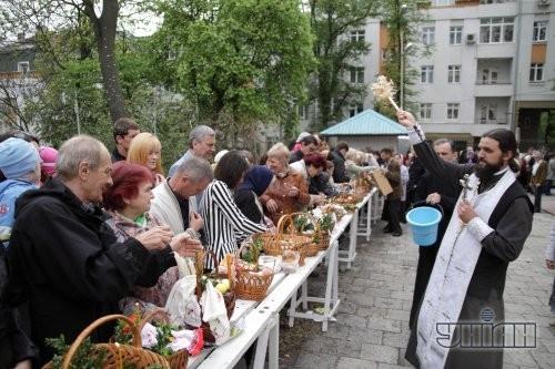 Священнослужитель освящает пасхальные корзины накануне празднования Воскресения Христово во Львове