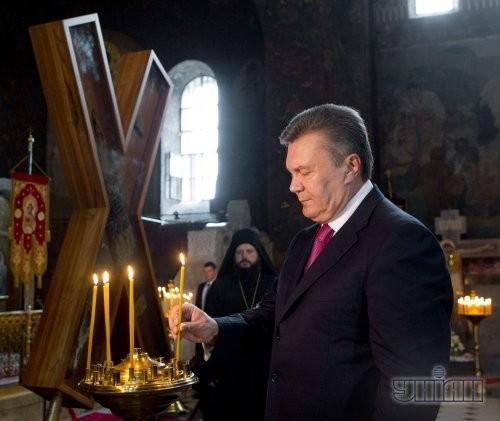 Президент Украины Виктор Янукович ставит свечу возле Креста апостола Андрея Первозванного в Трапезном храме Киево-Печерской Лавры