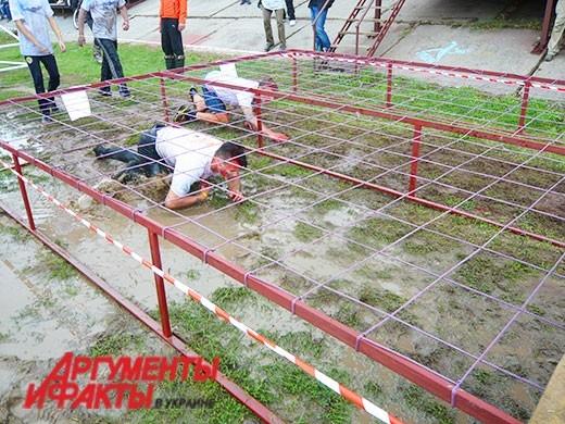 Участники пролазили под металлической сеткой в хлюпающей грязи