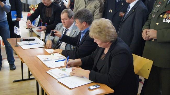 Главный федеральный инспектор в Смоленской области Ольга Окунева и почетные гости соревнований проводят церемонию гашения конвертов с портретом Григория Бояринова