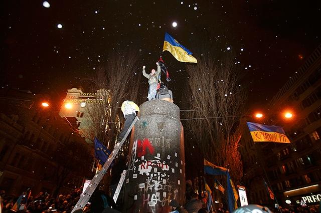 Затем активисты забрались на постамент, с которого начали размахивать национальным флагом Украины.