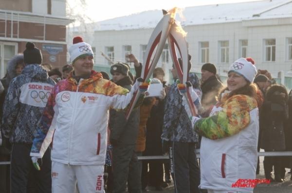 Факелоносцы бережно передают Олимпийский огонь из рук в руки.