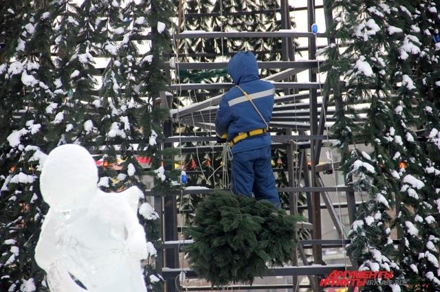 Рабочие, рискуя жизнью, карабкаются науерх прямо по елке.