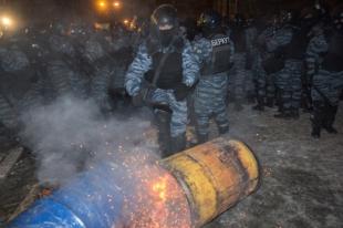 Сотрудники правоохранительных органов штурмуют баррикаду, построенную сторонниками евроинтеграции Украины.
