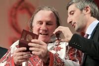 Французский актер Жерар Депардье (слева), которому было предоставлено российское гражданство, в национальной мордовской рубахе рассматривает свой российский паспорт со своим переводчиком на сцене Театра оперы и балета в Саранске.