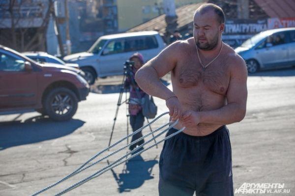 Прежде чем тянуть грузовик, Иван проверяет канаты на прочность.