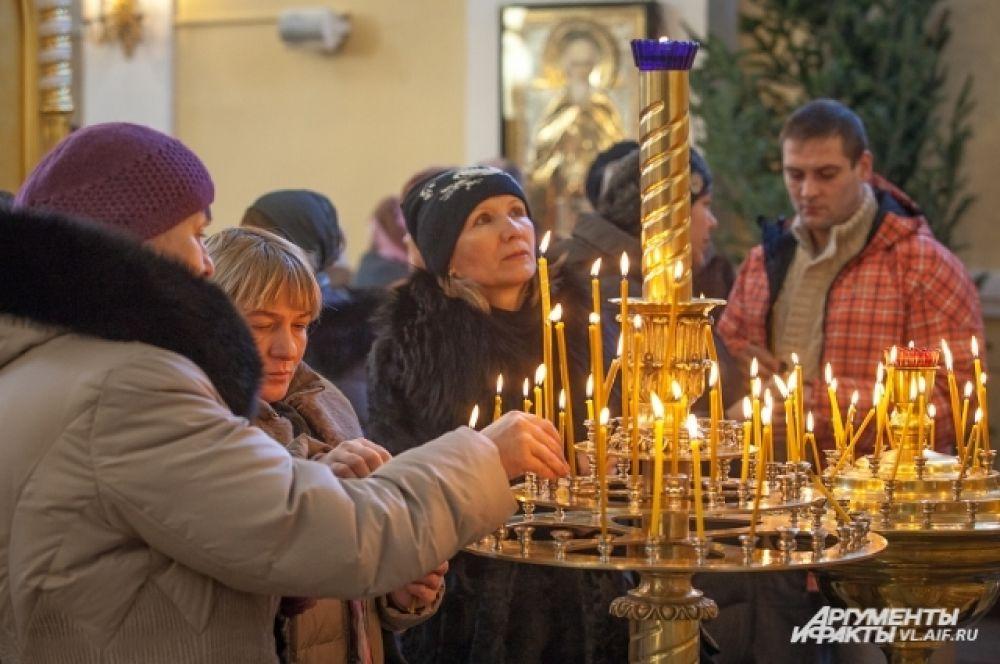 Прихожане ставят свечи за здравие родных.