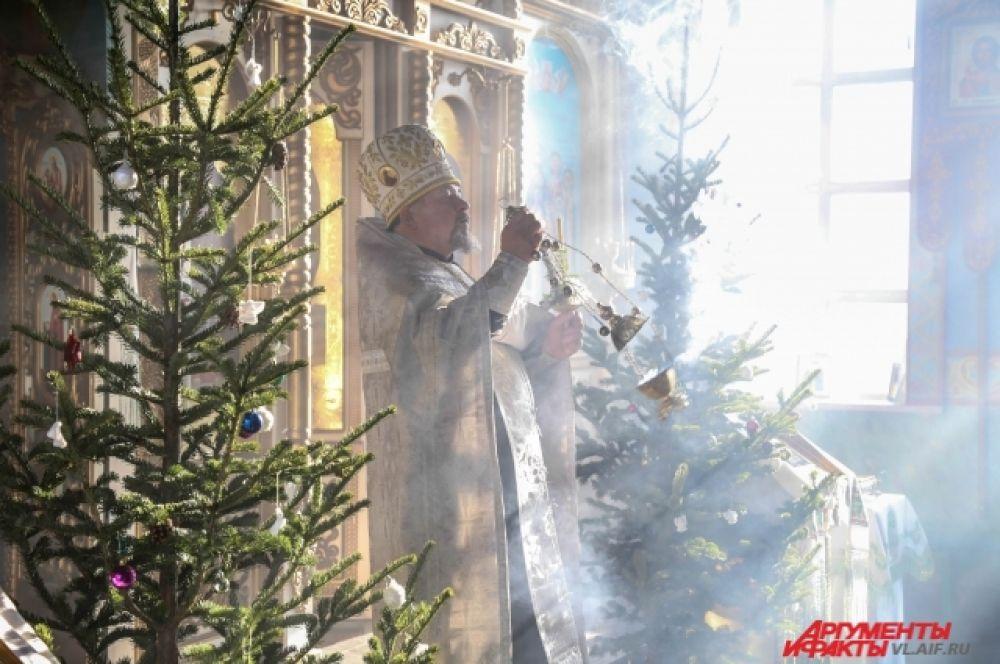 Батюшку озаряет свет праздника.