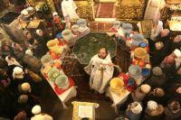 Верующие в храме Рождества Христова в южном Бутове набирают воду в Крещенский сочельник во время водосвятия.