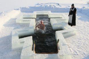 Мужчина купается в проруби, вырезанной в форме православного креста, в праздник Крещения Господня на озере Вяча под Минском.