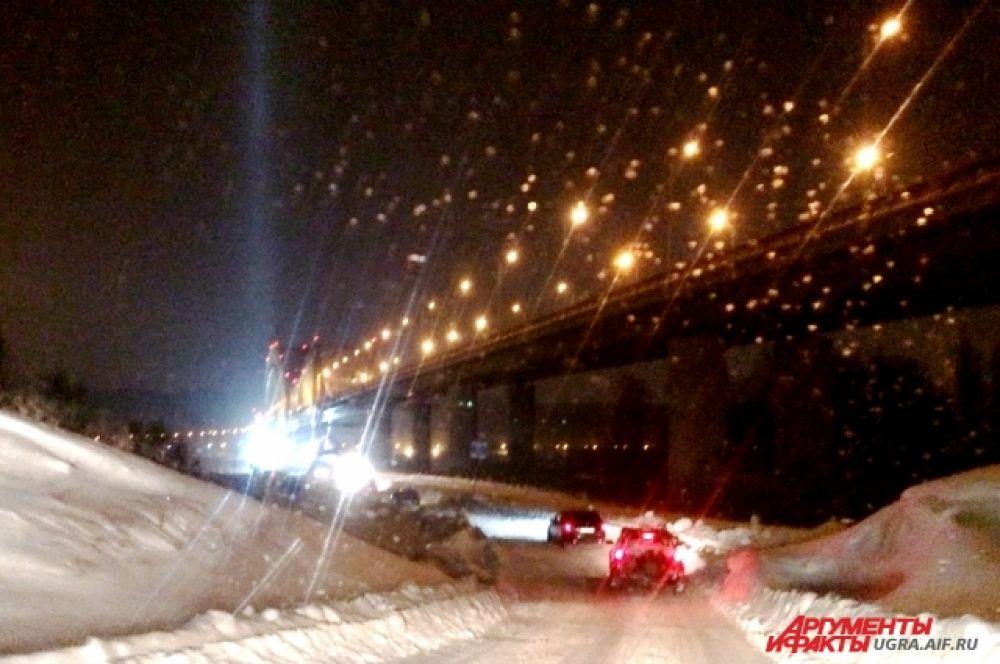 К проруби на Иртыше ведет дорога, по которой целый день снуют автомобили. Стоянка для транспорта возле реки заполнена.