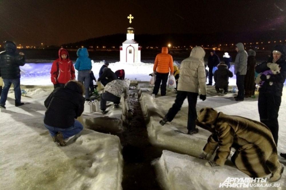 На Иртыше тем временем не менее оживленно, чем в Храме. Специально во льду вырублена прорубь в форме православного креста, откуда прихожане черпают святую речную воду ведрами.