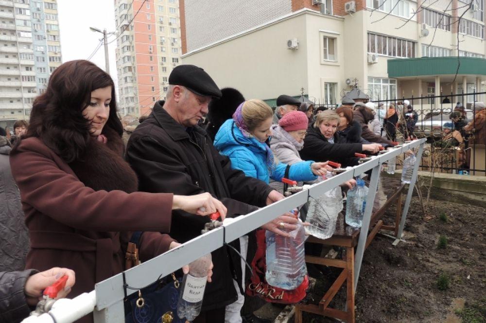 Прихожане набирают освященную воду.