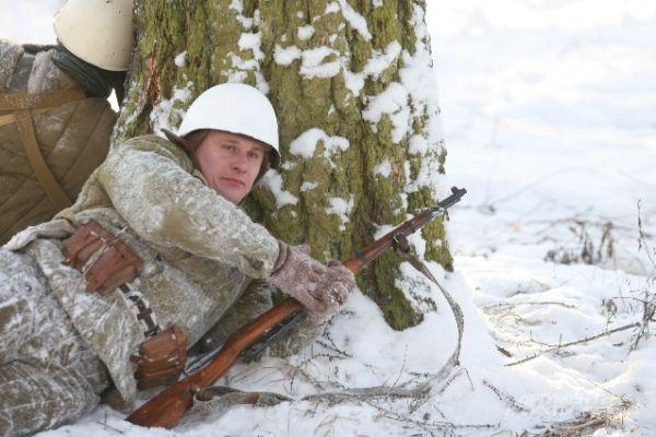 Участник реконструкции укрылся за деревом, чтобы не попасть под прицел врага.