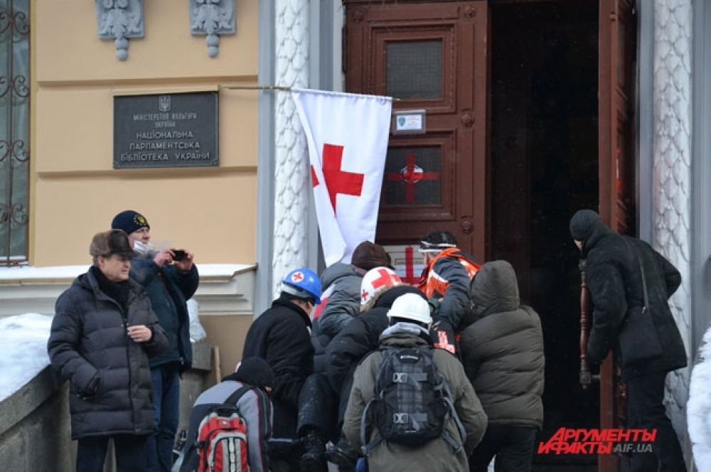 Раненых активистов Евромайдана несут в медпункт парламентской библиотеки