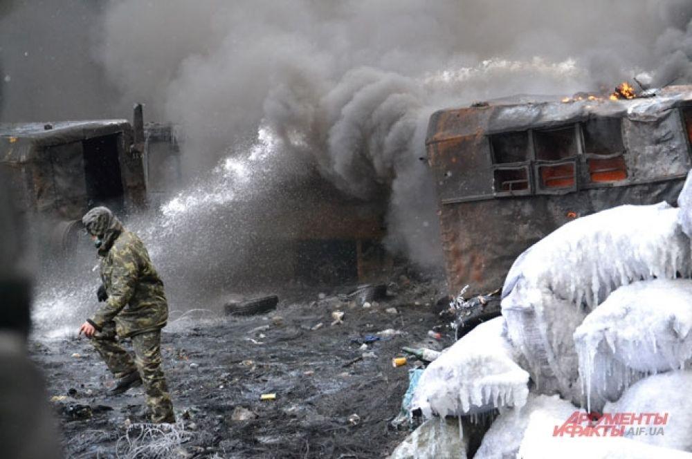 Пожарные пытаются потушить горящие шины