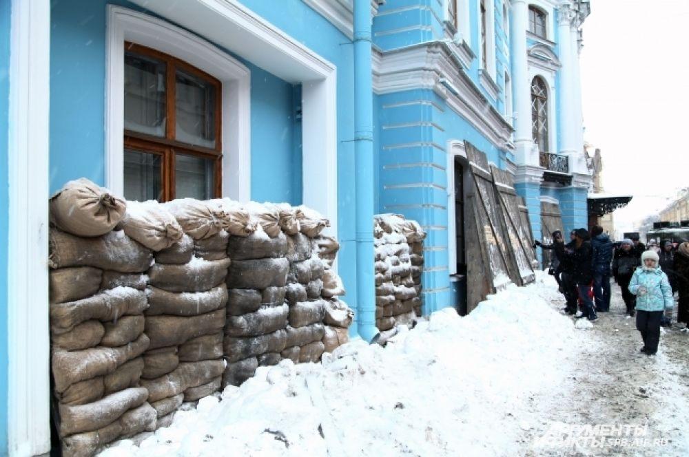 Фасады зданий закрыты досками и мешками с песком
