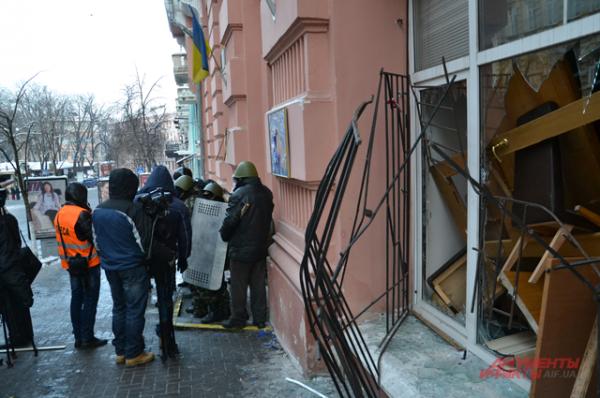 В разбитых окнах видно наспех установленные баррикады из подручных материалов