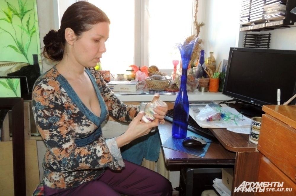 Гюзель наносит на бутылку узор.