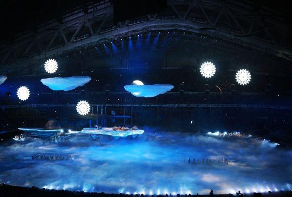Пять огромных снежинок, постепенно увеличиваясь, превращаются в олимпийские кольца