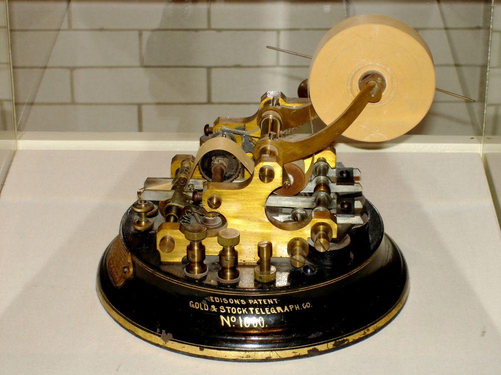 В 1869 году в свет вышел первый в истории тикерный аппарат – устройство для передачи котировок акции по телефонным или телеграфным проводам. С помощью тикерной машины на непрерывной бумажной ленте печатались текущие котировки ценных бумаг со скоростью один символ в секунду. Именно с этого момента названия компаний в биржевых сводках начали сокращать – такие сокращения называют тикерами.