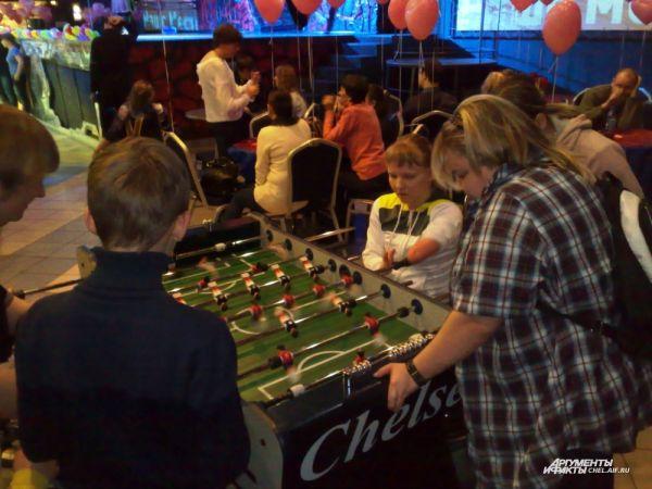Болельщики и волонтеры помогают играть в настольные игры.