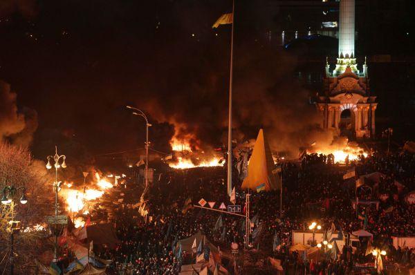 С использованием бронетехники и под прикрытием как минимум трёх водомётов силовики окружили Майдан и начали бросать в манифестантов световые гранаты и дымовые шашки.