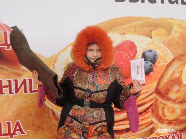 Самая юная участница конкурса на попадание валенком в цель получила поощрительный приз - сертификат на тысячу рублей в обувной магазин.
