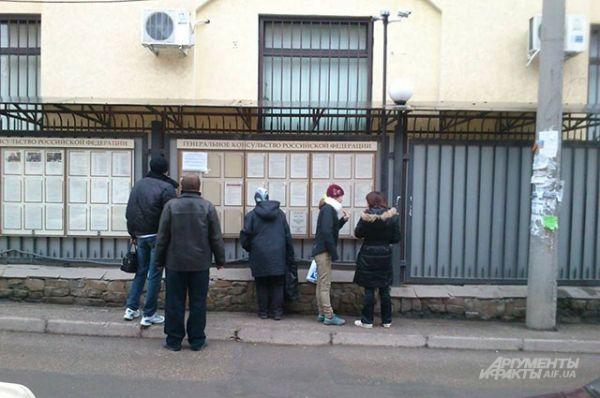 Возле Генконсульства России местные жители читают на стенде об упрощенном получении гражданства.