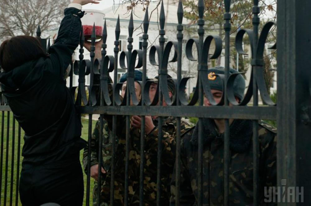 Женщина передает еду украинским военнослужащим, заблокированным на крымском военном аэродроме