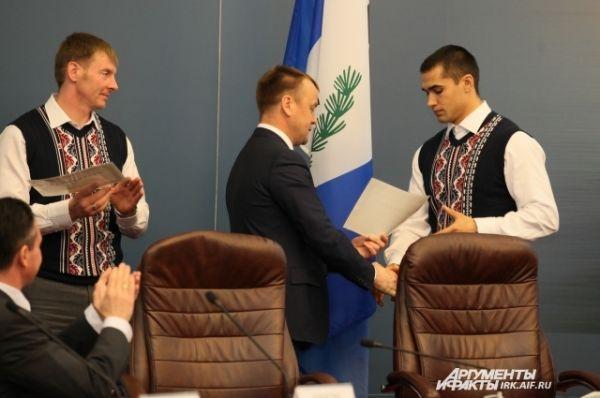 Губернатор жмет руку молодому спортсмену.