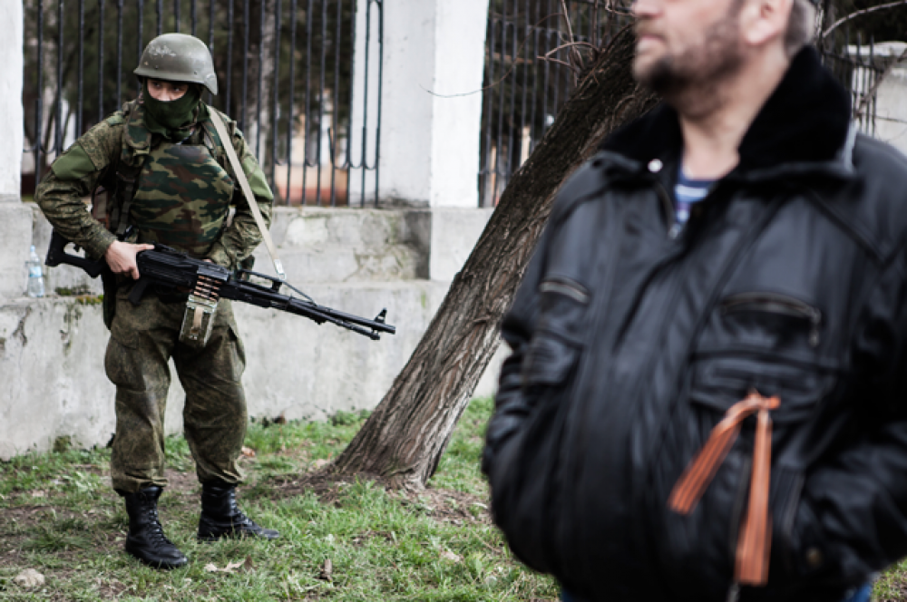 Хорошо вооруженный неизвестный солдат стоит на страже у штаба береговой охраны на улице Маркса Карла в Симферополе