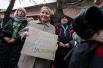 Проукраинская активистка держит плакат с надписью «Путин, руки прочь от Украины!»