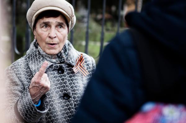 Пожилая женщина спорит с протестующими по поводу событий в Крыму