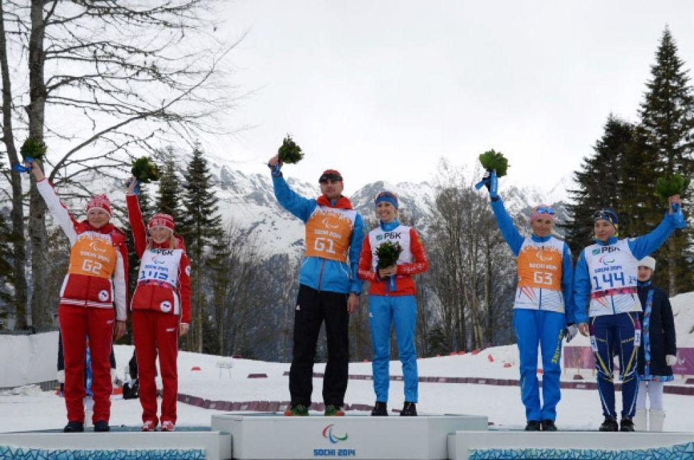 Российским триумфом 8 марта завершилась биатлонная гонка на шесть километров – Михалина Лысова (в центре с ведущим Алексеем Ивановым) одержала победу, а Юлия Будалеева (слева с ведущей Татьяной Мальцевой) финишировала второй.