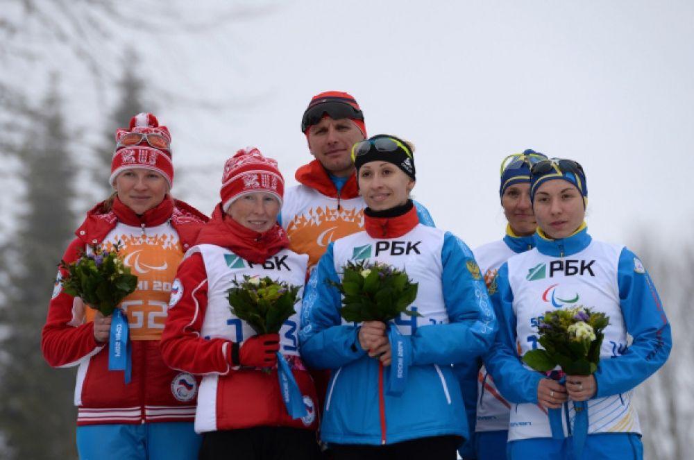 Свою вторую золотую медаль в Сочи биатлонистка Михалина Лысова (в центре с ведущим Алексеем Ивановым) выиграла на дистанции 10 км в категории «с нарушением зрения». Второй к финишу пришла другая россиянка – Юлия Будалеева (слева с ведущей Татьяной Мальцевой).