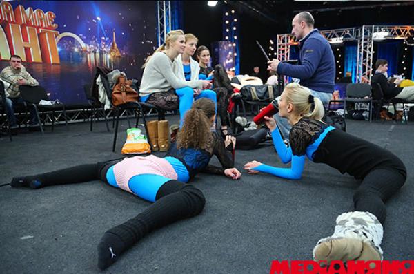 Девушки разминаются перед выходом на сцену, наблюдая за остальными конкурсантами