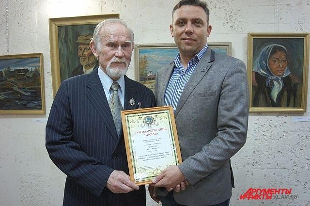 Художнику Юрию Волкову вручают благодарственное письмо.