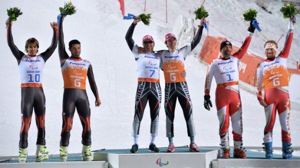 Призеры в слаломе в классе B 1-3 (слабовидящие) среди мужчин в соревнованиях по горнолыжному спорту на XI Паралимпийских зимних играх в Сочи, во время цветочной церемонии.