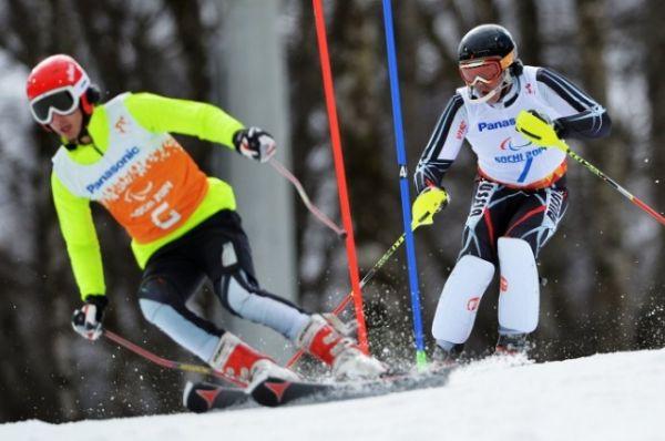 Валерий Редкозубов (Россия) и ведущий Евгений Героев (слева) на трассе слалома в первой попытке в классе B 1-3 (слабовидящие) на соревнованиях по горнолыжному спорту среди мужчин.