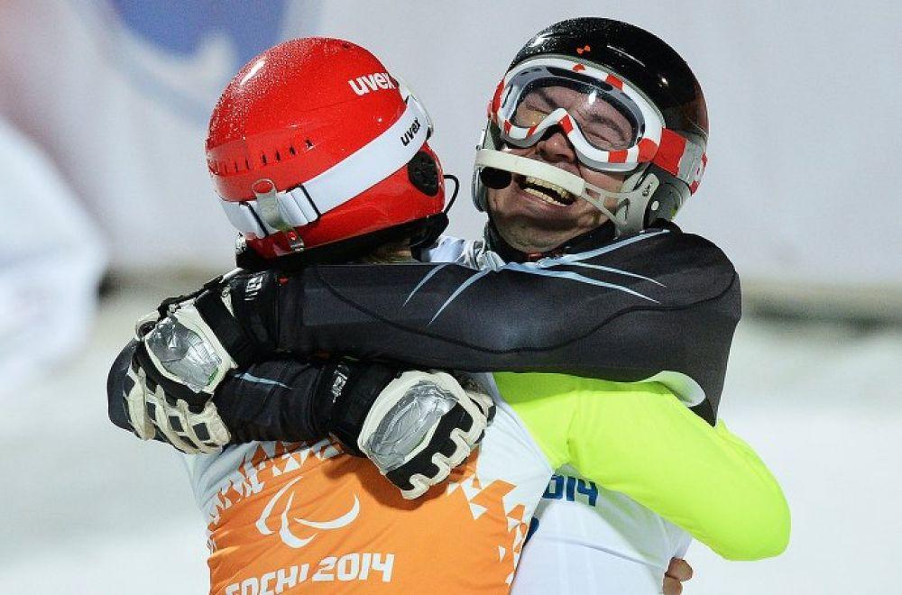 Валерий Редкозубов (Россия) и ведущий Евгений Героев (слева) после финиша слалома во второй попытке в классе B 1-3 (слабовидящие) на соревнованиях по горнолыжному спорту среди мужчин.