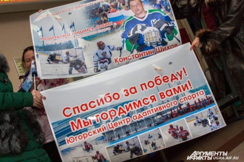 В аэропорту чемпиона встречали болельщики и сотрудники центра адаптивного спорта и следж-хоккейного клуба «Югра», с плакатами и цветами.