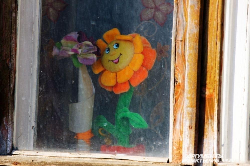 А на некоторых окнах - цветы плюшевые.