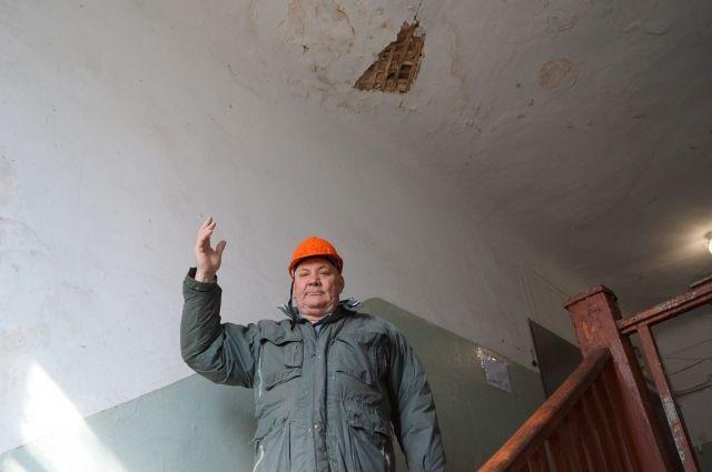 Жители аварийного дома выходят из квартир в касках