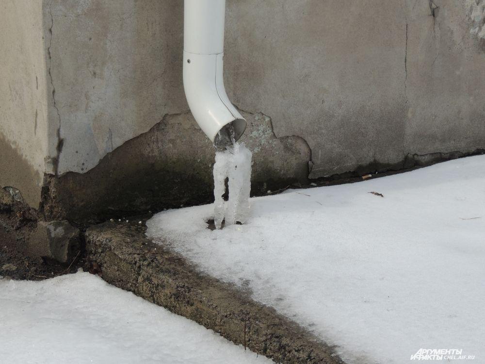 Снег на крышах домов тает, но, стекая по водосточным трубам, вода замерзает при минусовой температуре.