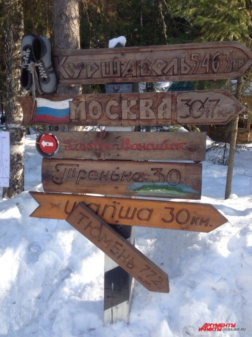 На входе в питомник стоит резной указатель, на котором выведены расстояния до Москвы, Тюмени и даже Куршавеля.