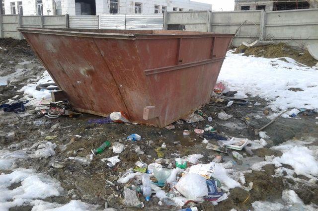 Груда мусора лежит возле общественной остановки